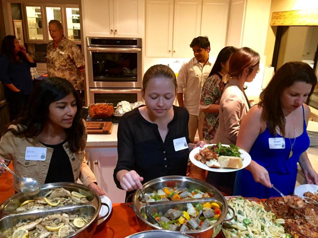 Mihaylo College students enjoy a diverse selection of cuisine at an alumnus' house as part of the Dinner With 12 Titans program.