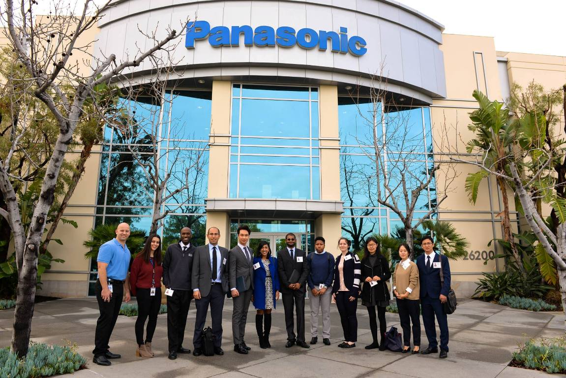 A group of Cal State Fullerton Mihaylo College graduate students, faculty and staff outside the entrance of the Panasonic building in Lake Forest, California.