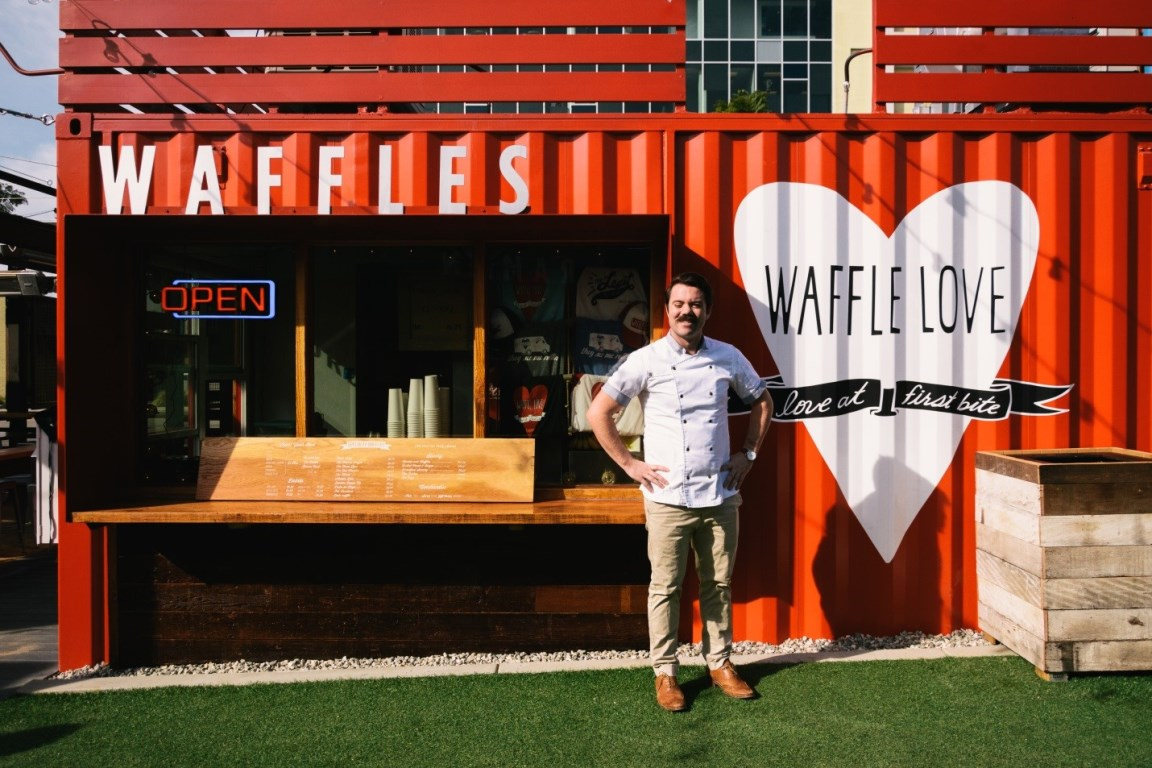 A cook stands outside Waffle Love at SteelCraft in Long Beach, a food court made of recycled shipping containers.