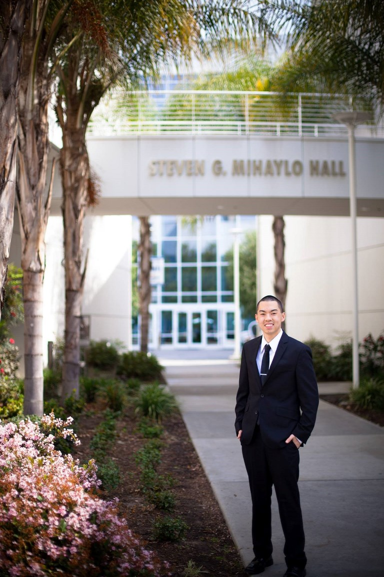 Mihaylo College alumnus Terence Yee '16 poses in professional attire beneath the sign at the entrance to the Mihaylo Courtyard.