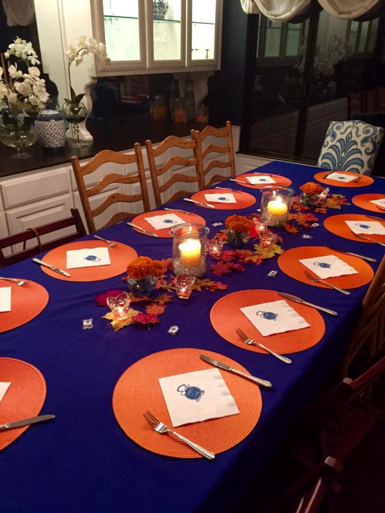 An empty dinner table with the silverware and plates set at the home of a Mihaylo College alumnus participating in the D12 program.