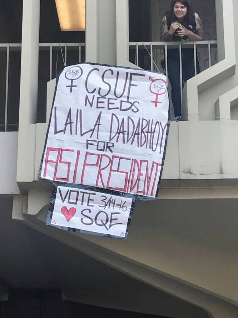 A female student stands on a balcony where a sign supporting the Dadabhoy/La campaign dangles below.