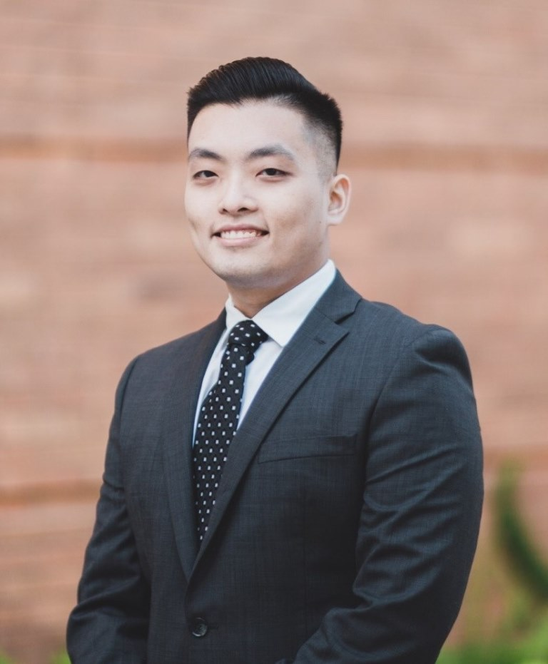 Mihaylo student Mark Tran '17 poses in suit and tie at his internship at the City of Long Beach.