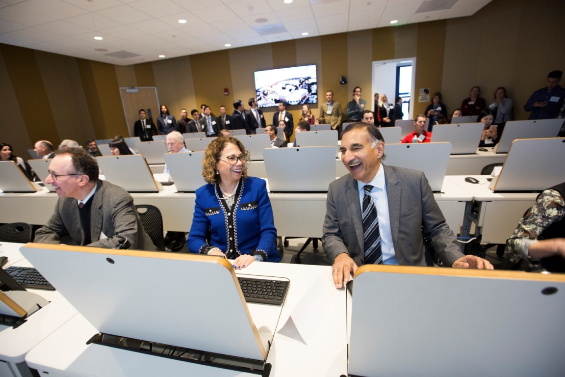 Academic and business leaders sit behind the Bloomberg business terminals at the newly opened Titan Capital Management lab at Cal State Fullerton's Mihaylo College of Business and Economics.