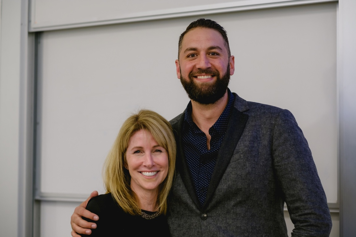 Mihaylo College alumnus Kevin Rohani and Entertainment and Hospitality Management director Kim Tarantino pose in front of a whiteboard in a classroom.