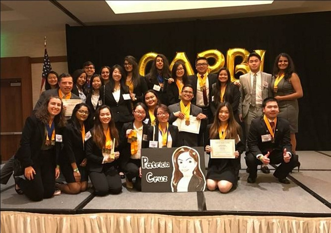 Members of Cal State Fullerton's chapter of Phi Beta Lambda pose as a group while holding club insignia.