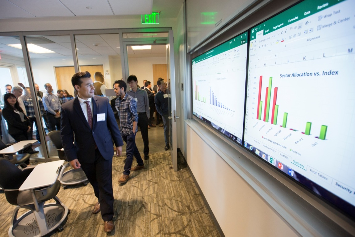 A male student in professional attire looks at the digital charts at Titan Capital Management Lab at Cal State Fullerton's Mihaylo College of Business and Economics.