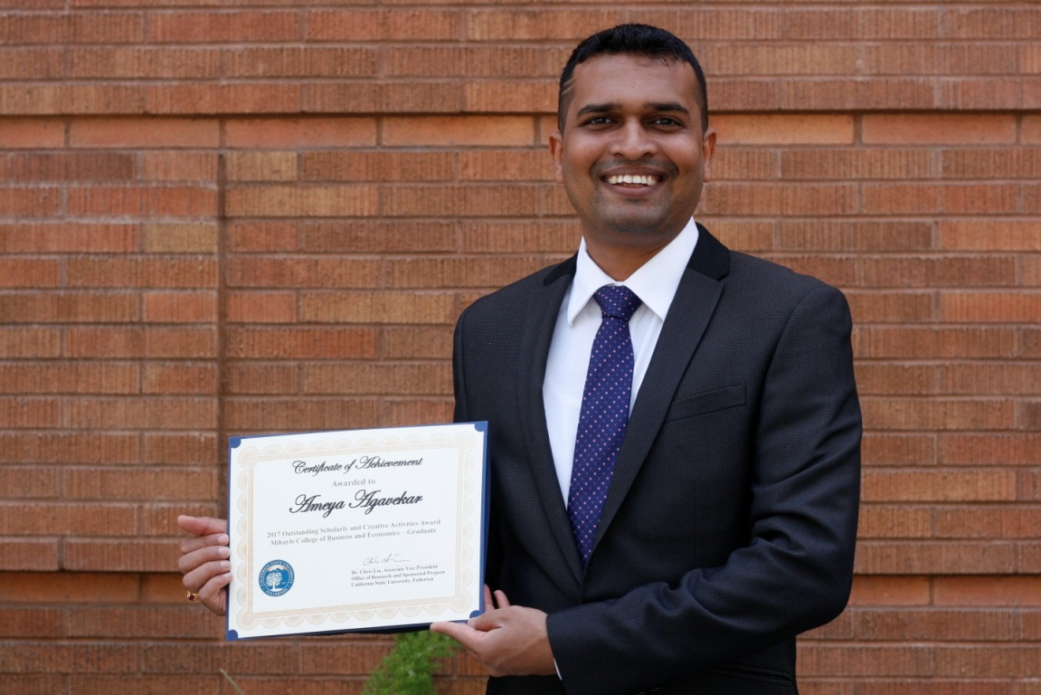 Mihaylo College graduate student Ameya Agavekar holds his Outstanding Student Scholarly and Creative Activities Award while standing in front of a brick wall.