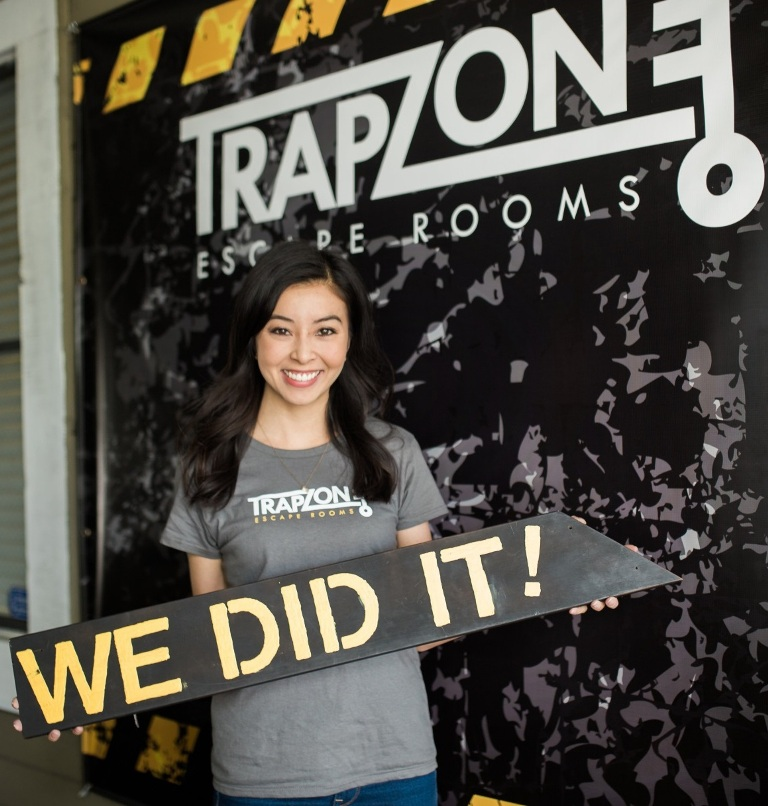 """Julie Hom, a Mihaylo College alumna, holds a sign reading """"We Did It!"""" in front of the logo of her Costa Mesa, California, TrapZone Escape Rooms."""