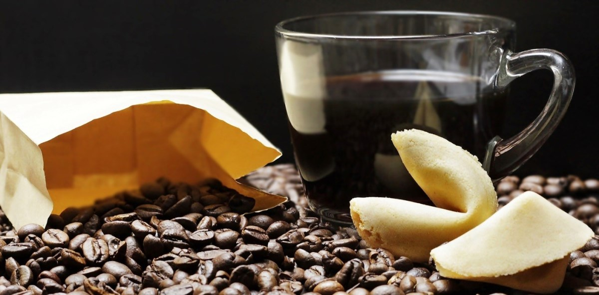 Coffee beans, a clear glass of hot coffee and fortune cookies.