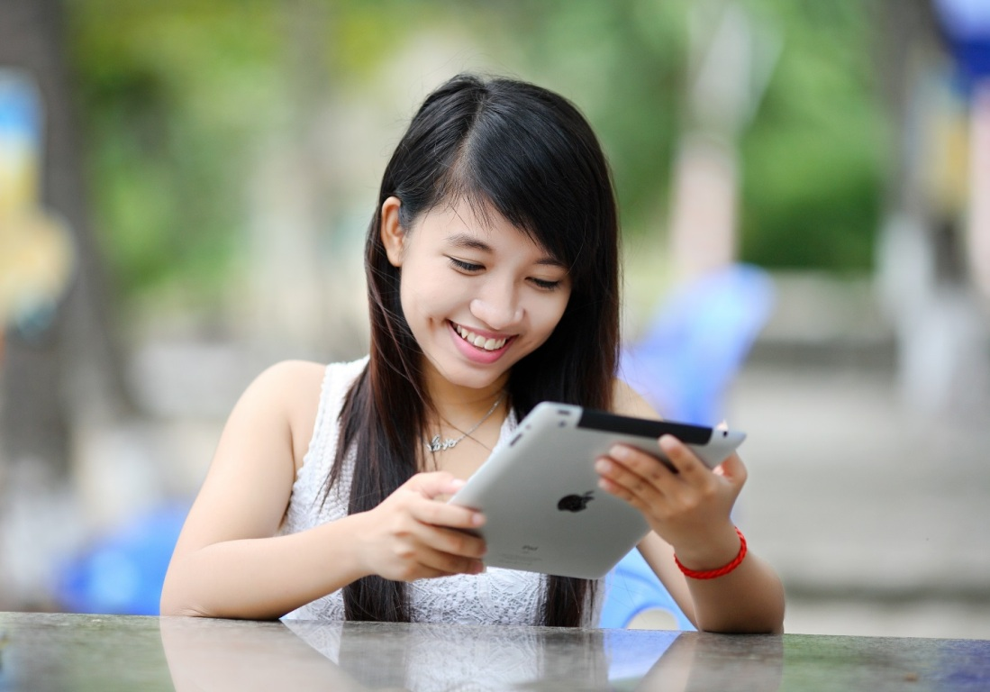 An Asian girl or young woman uses an iPad tablet device.
