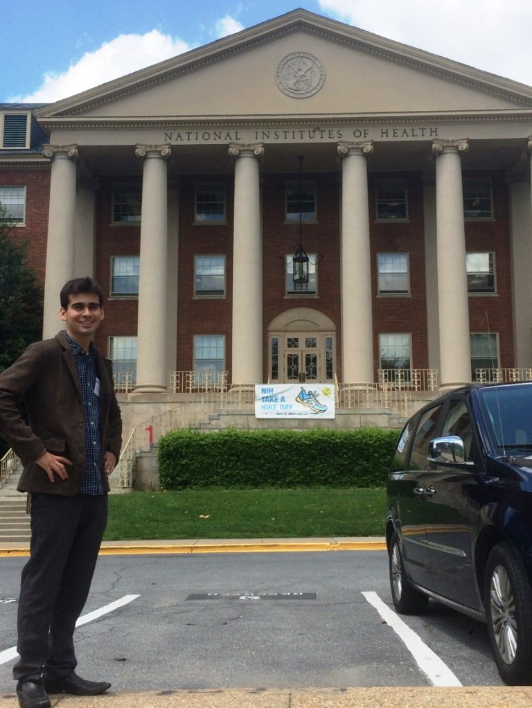 Mihaylo College grad Ruben Velasco '17 poses in front of the National Institutes of Health (NIH) building in Maryland.