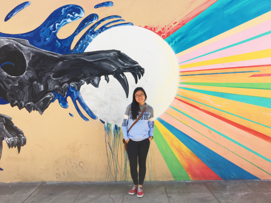 Gloria Chu in front of a mural