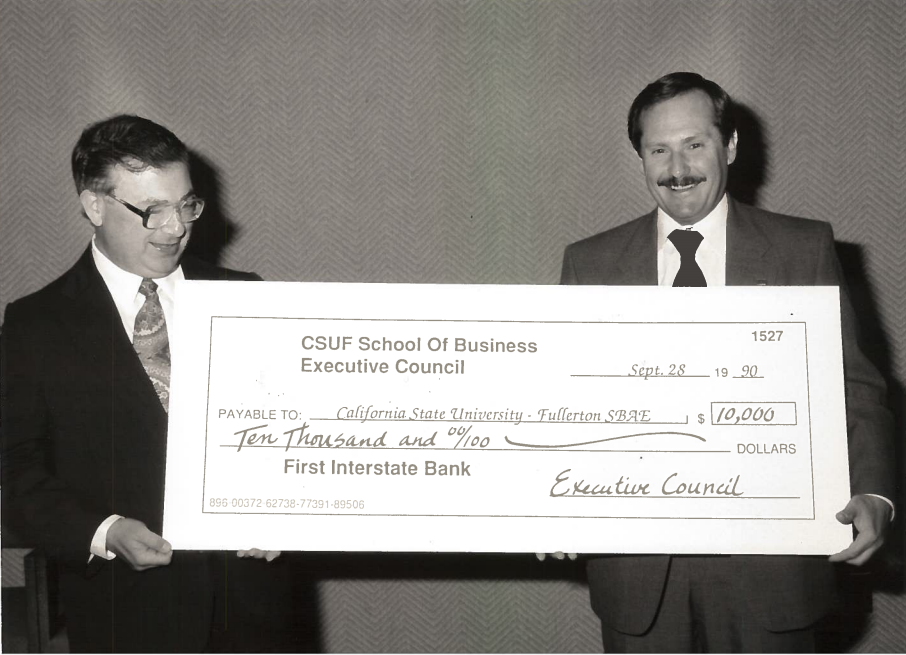Vic Hausmaninger '64 (right) presents a check on behalf of the Executive Council for Cal State Fullerton's business program in 1990.