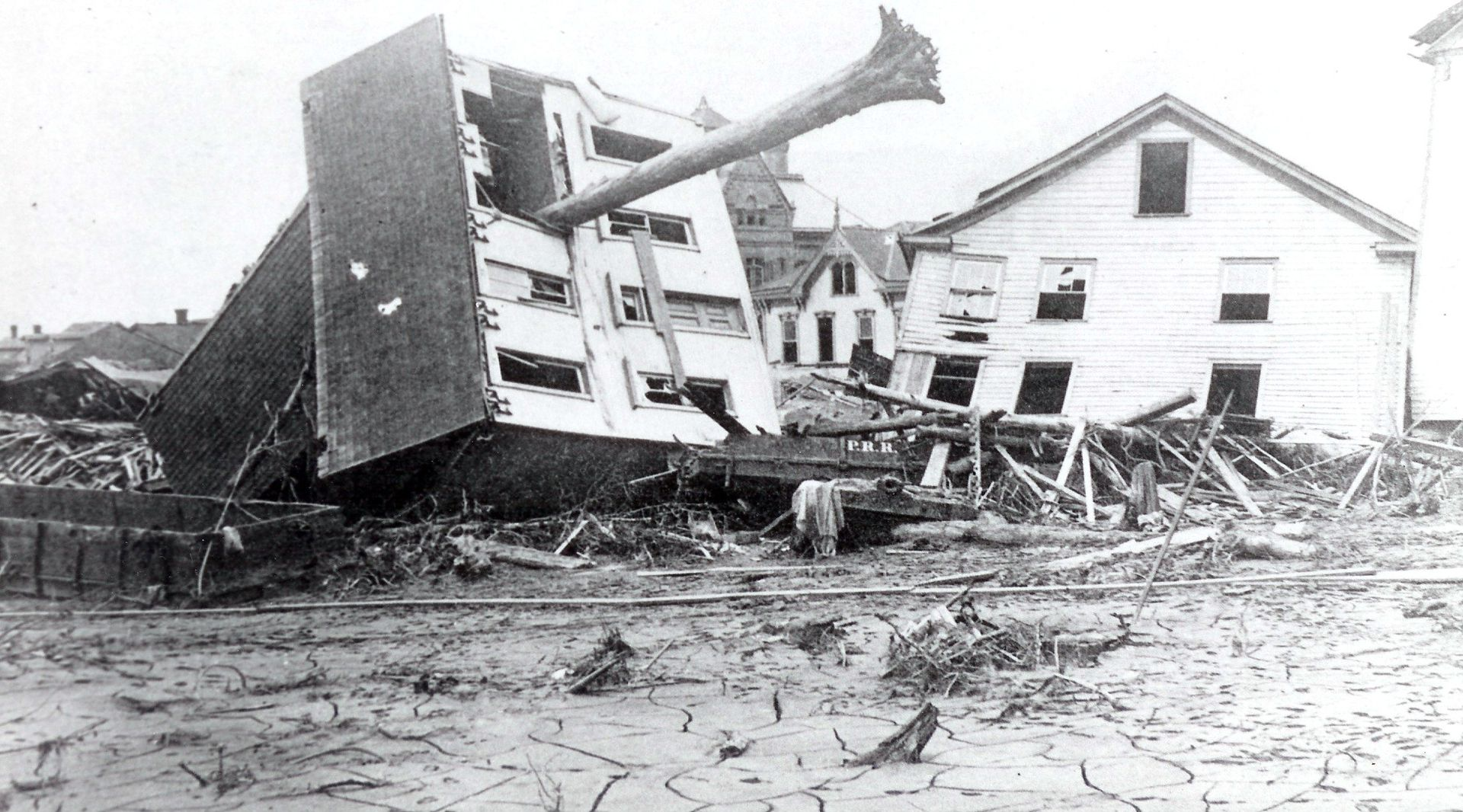 A tree juts out of an upended home in Johnstown, Pennsylvania, after the devastating 1889 flood, one of the deadliest natural disasters in American history.
