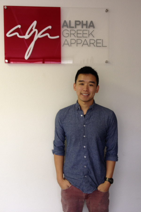Mihaylo Grad Jason Liu stands in front of the logo of his Alpha Greek Apparel startup in Fountain Valley, California.