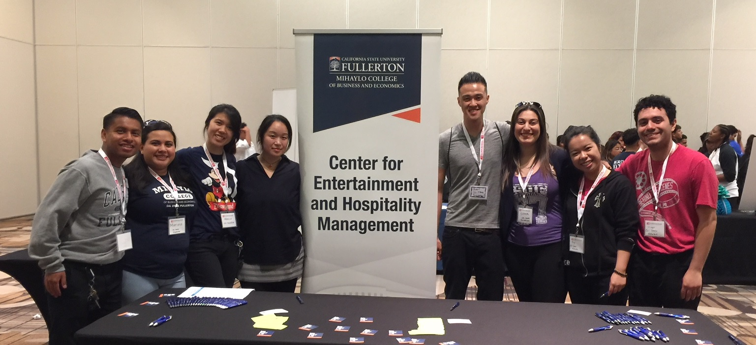 Mihaylo College students and faculty pose around a table at the Experience Hospitality event in Anaheim, California, in April 2018, which exposed local high school students to careers in the restaurant, hospitality and entertainment industries.