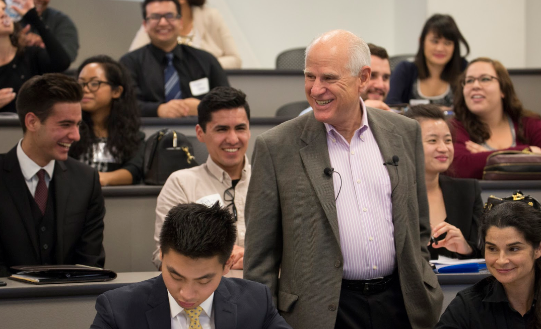 A smiling Steven Mihaylo walks among an audience of Leadership Scholars students at Cal State Fullerton in March 2015.