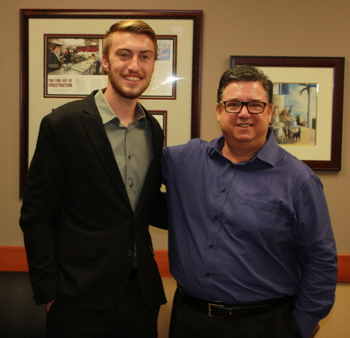 Jerry Conrey and Mihaylo College entrepreneurship student Tristan Starkweather pose in the Tustin office of Conrey Insurance Brokers.