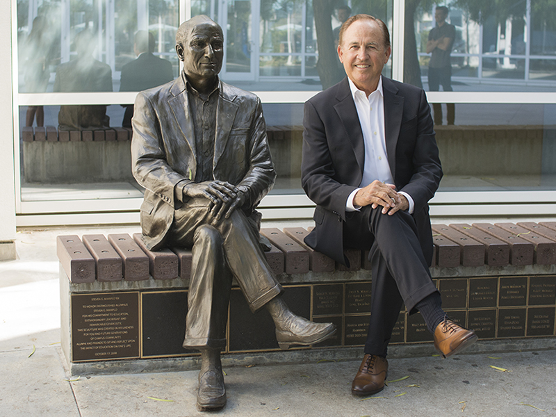 CSUF Mihaylo Center for Real Estate Director Bob Osbrink seated in the Mihaylo Hall courtyard next to a statue of college namesake Steven G. Mihaylo '69.