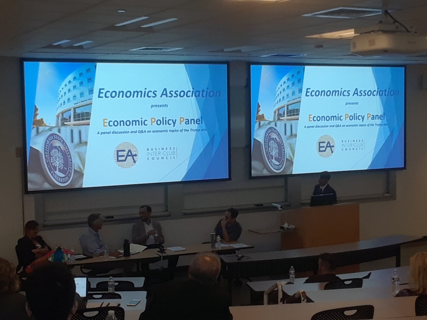 A group of four panelists discuss economic policy in a classroom at the Steven G. Mihaylo Hall at Cal State Fullerton.