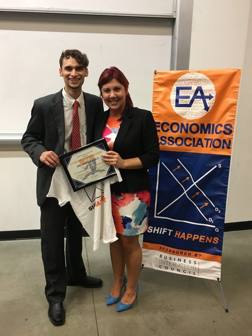 Micah Herman, president of the Cal State Fullerton Mihaylo College Economics Association, stands next to Economics Associate Professor Mira Farka, who holds a certificate that he has just presented to her.