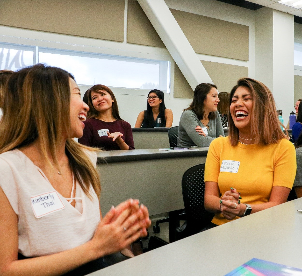 Aspiring businesswomen laugh in a class taught at the Women's Leadership Program at CSUF Mihaylo College.