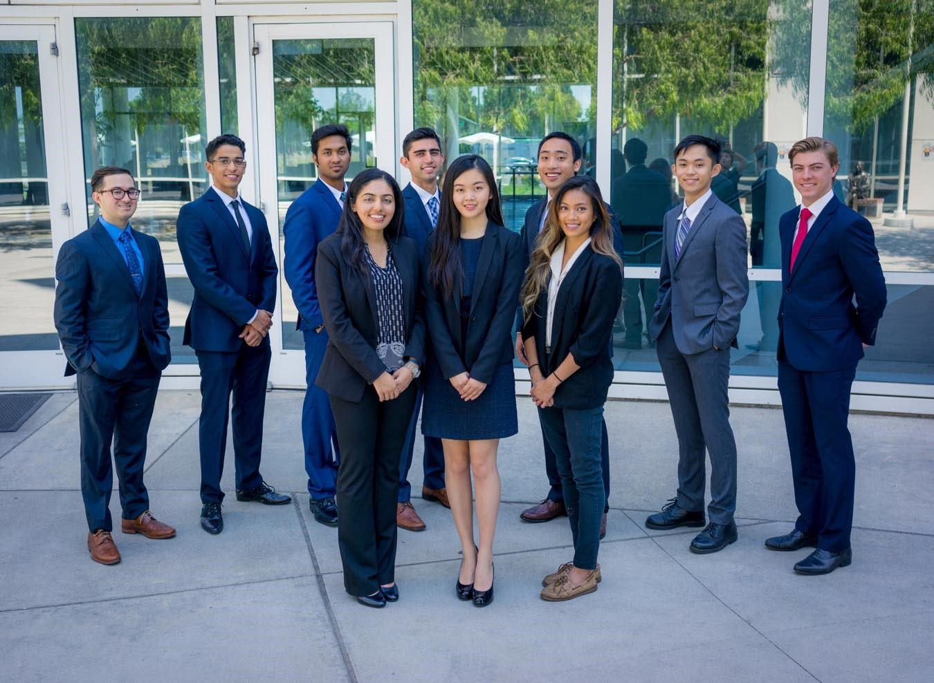 Members of the CSUF Mihaylo College Finance Association (FA) pose in front of the Steven G. Mihaylo Hall in professional business attire.