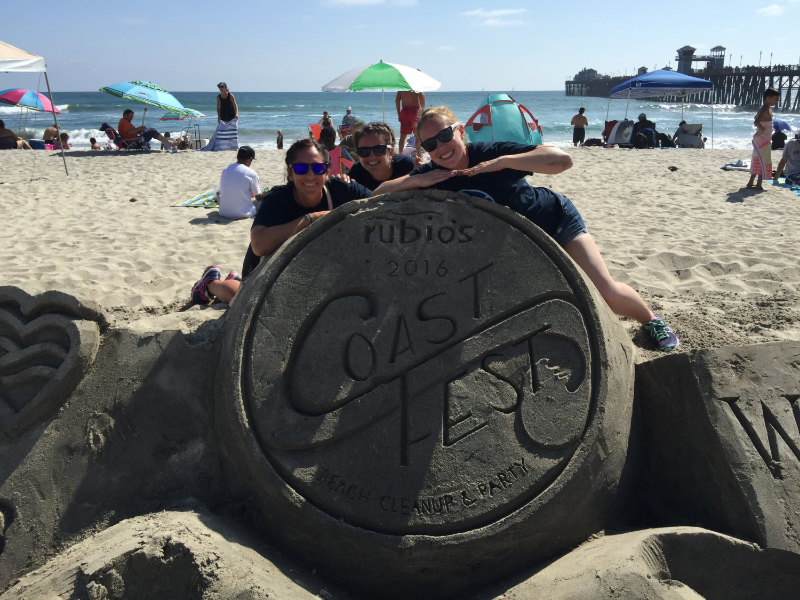 A sandcastle emblazoned with the logo of Rubio's Coastal Grill and the 2016 Coast Fest cleanup event.