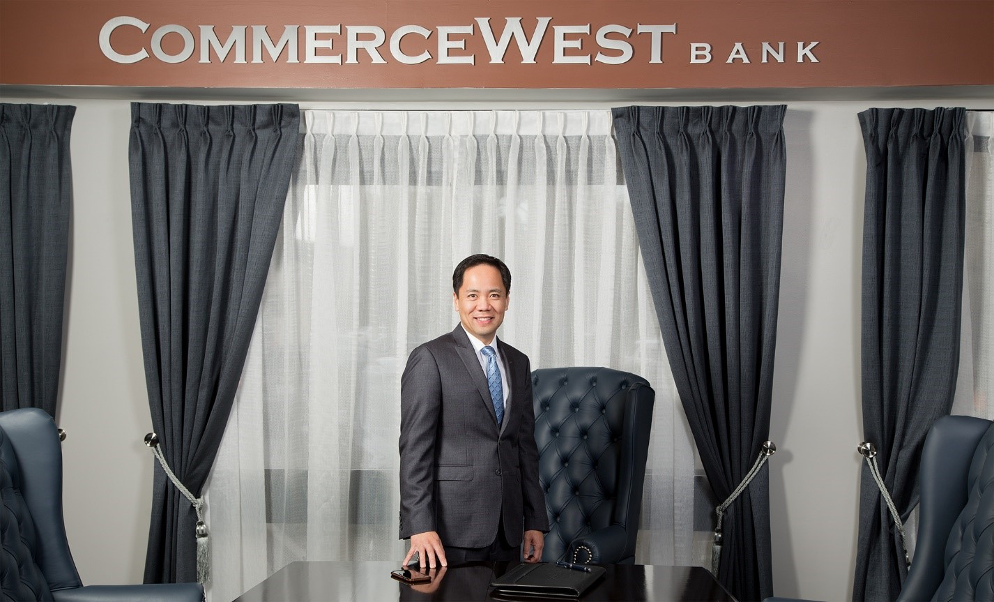 Ivo Tjan, president and founder of CommerceWest Bank, stands behind a desk at the company's Irvine, California headquarters.
