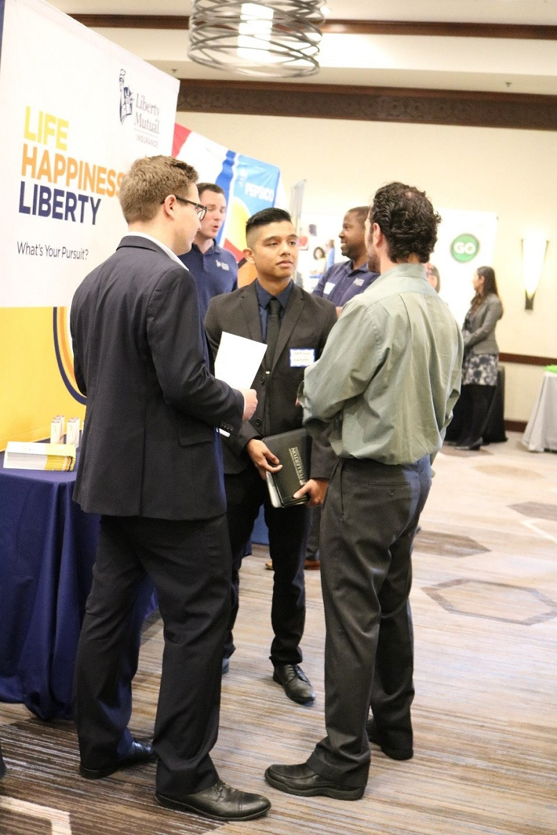 Cal State Fullerton Mihaylo College students talk with a recruiter at a Sales Leadership Center job fair event.