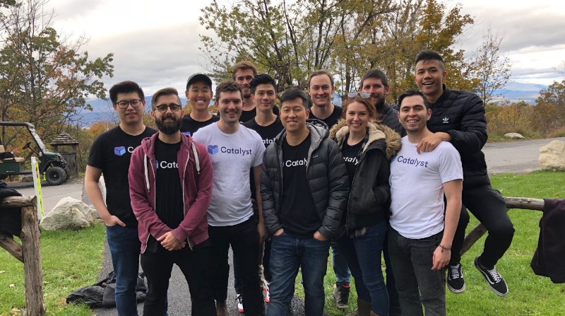 Kevin Chiu and other members of the Catalyst Software team stand in a field.