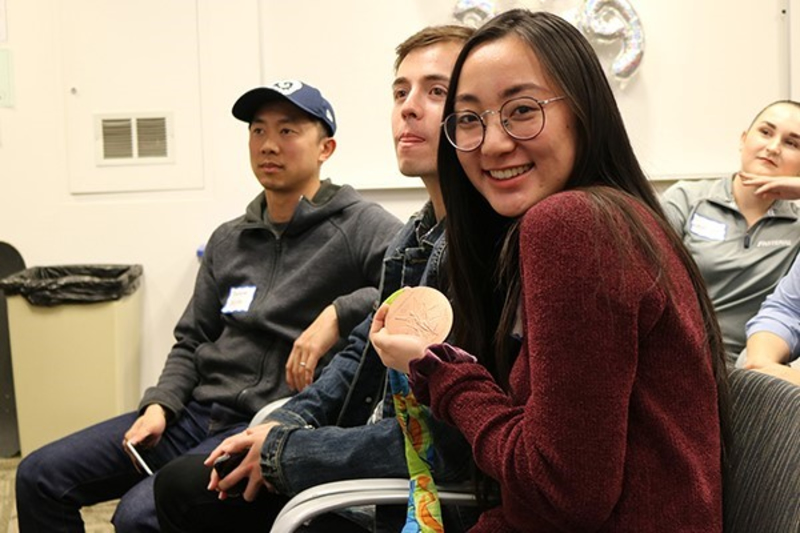 A Cal State Fullerton student holds a bronze Olympic medal belonging to Murphy Troy, a volleyball medalist who spoke on campus on Feb. 5, 2019.