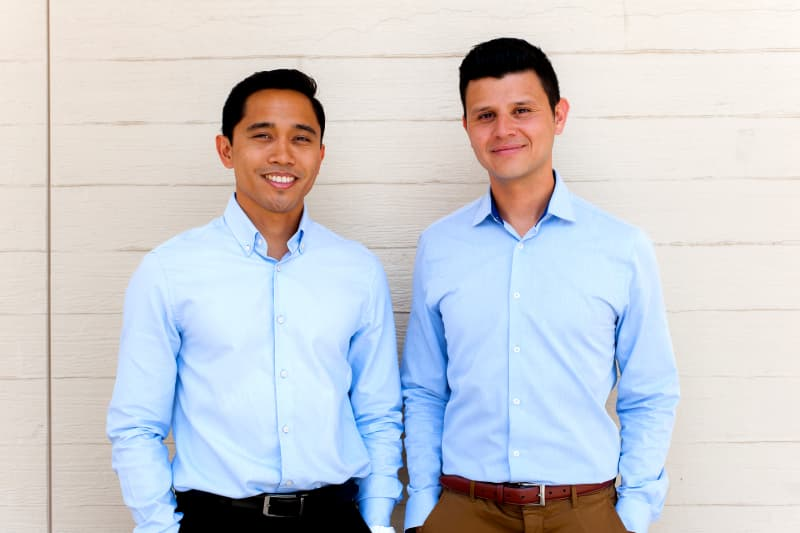 The co-founders of healthy cookie concept Nui Foods, Kristoffer Quiaoit and Victor Macias'09, pose wearing t-shirts emblazoned with the logo of their concept.