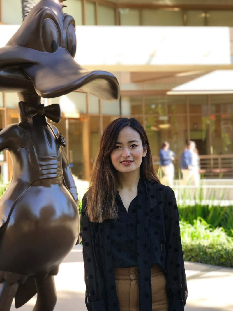 Passang Baro, senior financial analyst at Warner Bros., stands next to a sculpture of Donald Duck.