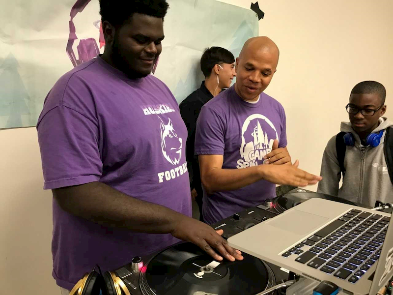 Amani Roberts demonstrates the use of music mixing equipment to up and coming DJ professionals.