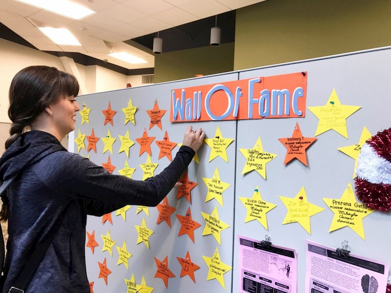 Jaqilyn Graff, a Cal State Fullerton business student, posts a star on the Wall of Fame at the school's Business Career Services, noting her accomplishment of an internship at Northwestern Mutual.