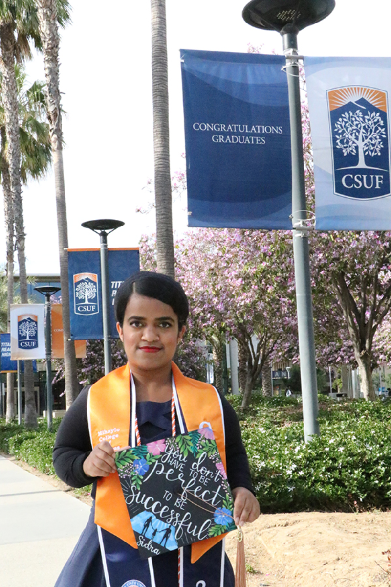 Sidra Syed poses in cap and gown at Cal State Fullerton