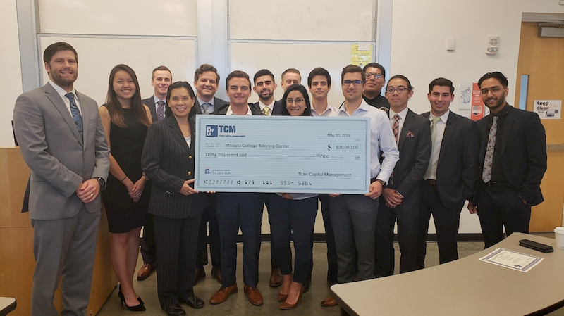 Cal State Fullerton Mihaylo College Titan Capital Management students present an oversized check to Emeline Yong, assistant dean for student affairs, on May 10, 2019.