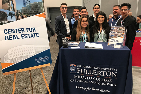 Cal State Fullerton students pose behind the Mihaylo College Center for Real Estate booth at RECon 2019 in Las Vegas