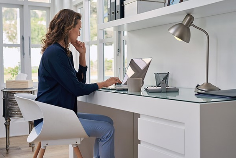 A young brunette woman in business casual attire utilizes a laptop computer in a modern home office.