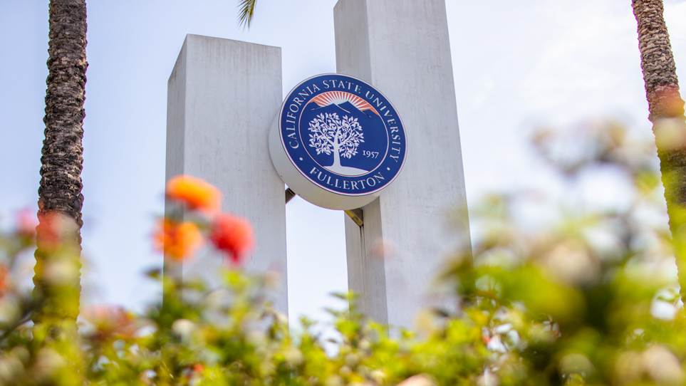 A sculpture with twin towers and the CSUF logo in between at Cal State Fullerton near the corner of State College and Nutwood.