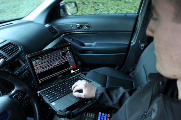 Inside a police car, an officer uses 10-8 Systems on a laptop.