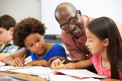 An African-American man teaching two young girls of color in a classroom in modern America.