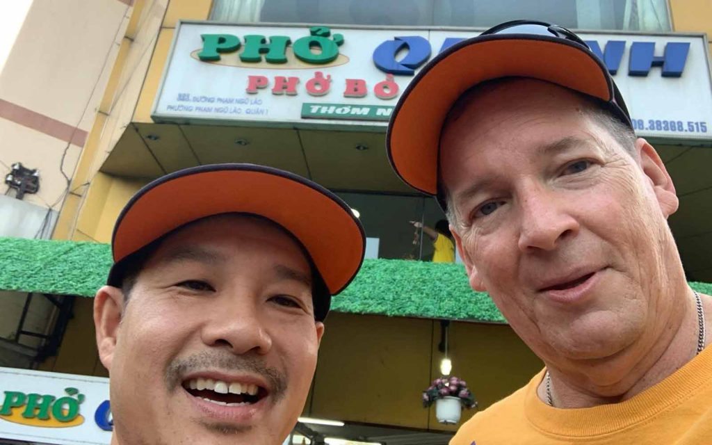 Ed Hart and Tam Nguyen from Cal State Fullerton pose in front of a pho restaurant in Ho Chi Minh City, Vietnam, in November 2019.