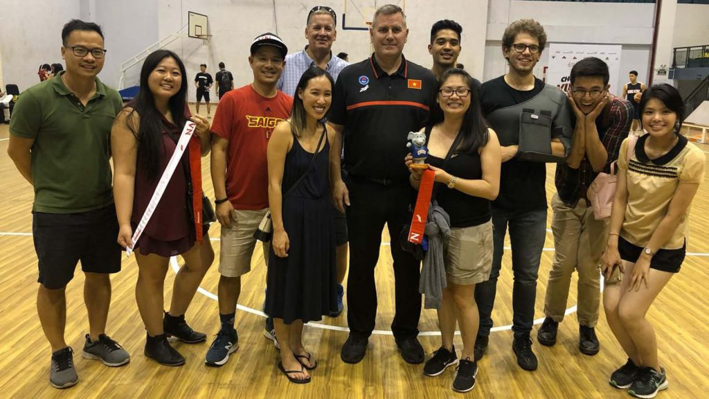 Cal State Fullerton students and staff take in a basketball game in Vietnam.