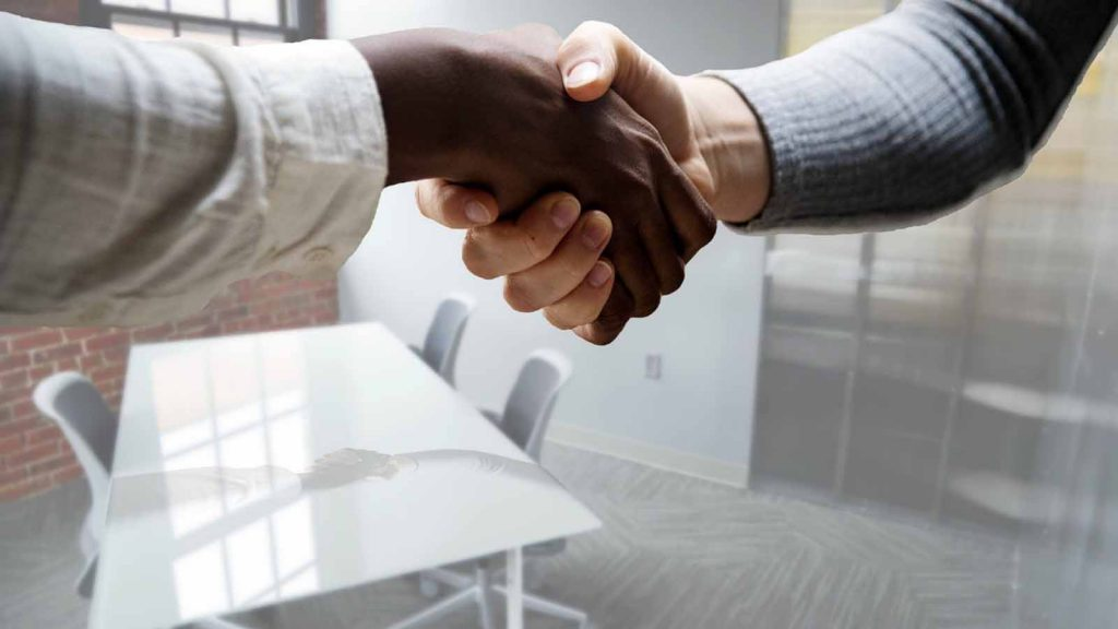 An African American and Caucasian shake hands at a workplace