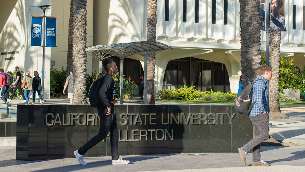 Students walk on campus in front of Cal State Fullerton sign.