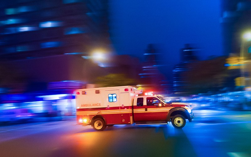 An ambulance rushes to a call in an urban area.