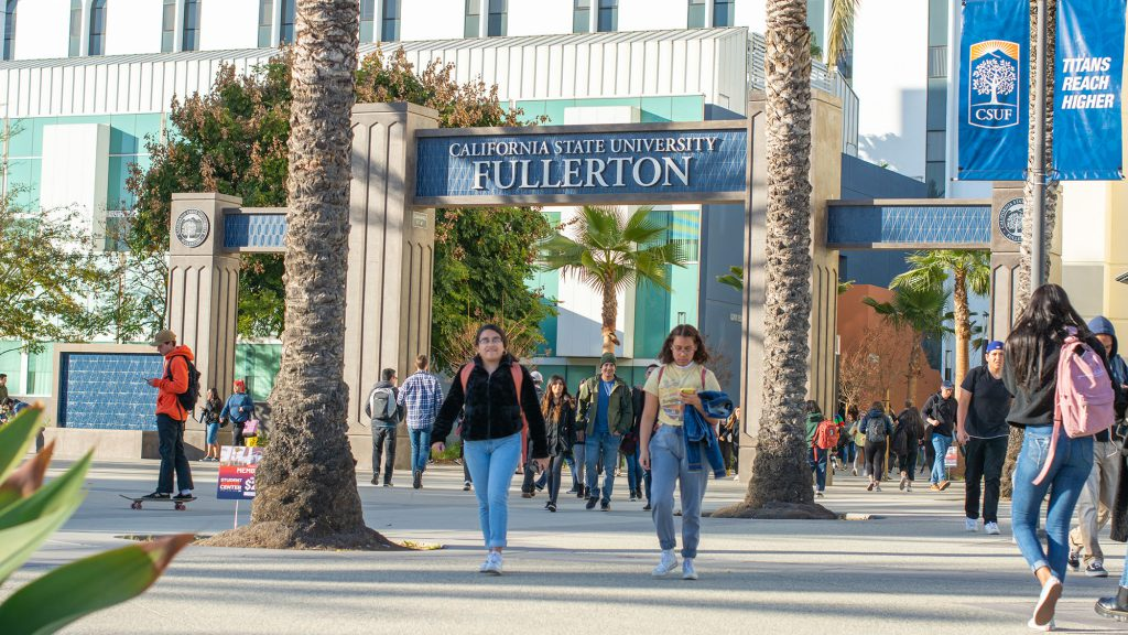 Students walking under Cal State Fullerton's entrance